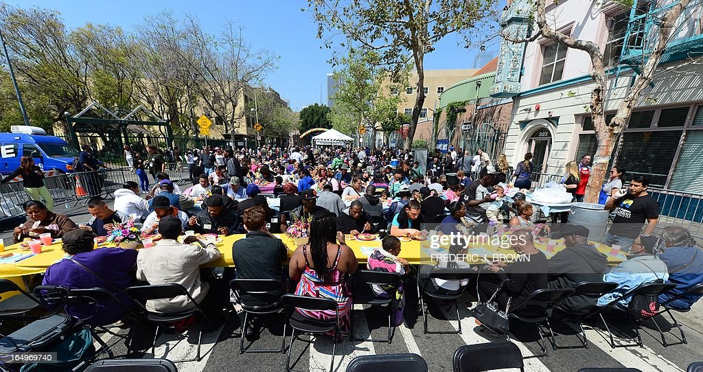 The homeless enjoy their Good Friday lunch at the Los Angeles Mission's Good Friday event on Skid Row on March 29, 2013 in Los Angeles, California. Celebrities and volunteers joined together in giving something back to this community of the homeless, among the largest in the US, who were fed a fully-prepared meal and had the opportunity to be given foot washing and hygiene kits. Foot washing, a symbolic ritual of humbleness and respect derived from Jesus Christ's washing of his disciples feet at the Last Supper, was offered by the Los Angeles Health Center and volunteers. AFP PHOTO/Frederic J. BROWN