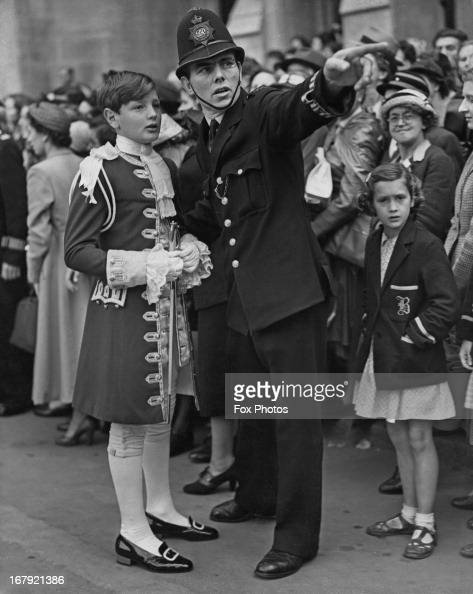 The Hon William Grosvenor page to Lord Churston gets directions from a policeman outside Westminster Abbey after a full dress rehearsal for the...