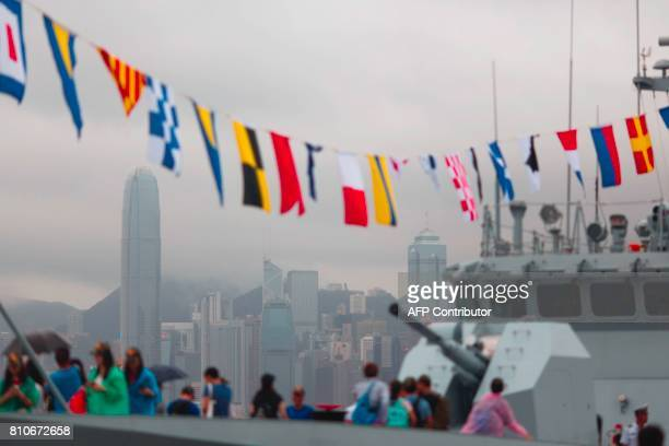 The Hong Kong skyline is seen past visitors on board the Chinese People's Liberation Army Navy frigate Huizhou at the Ngong Shuen Chau naval base on...