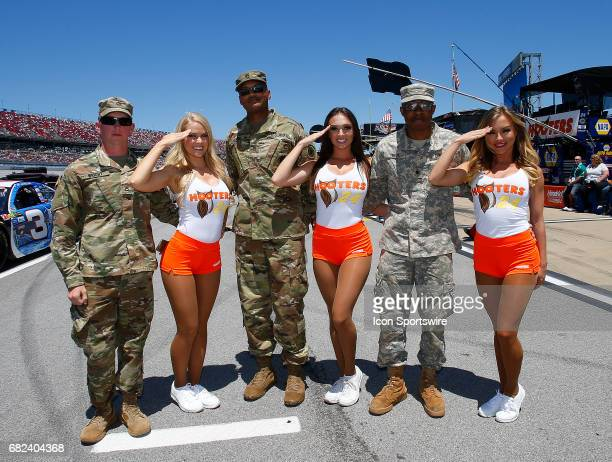 The Hooters girls pose with some US Army soldiers prior to the Monster Energy NASCAR Cup Series race on May 7 2017 at Talladega Superspeedway in...