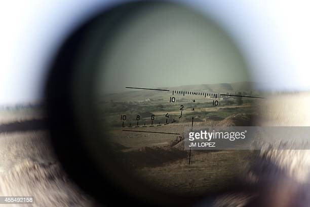 The horizon is seen through a telescopic rifle belonging to a Kurdish Peshmerga sniper on the front line in the Gwer district 40 kilometres south of...