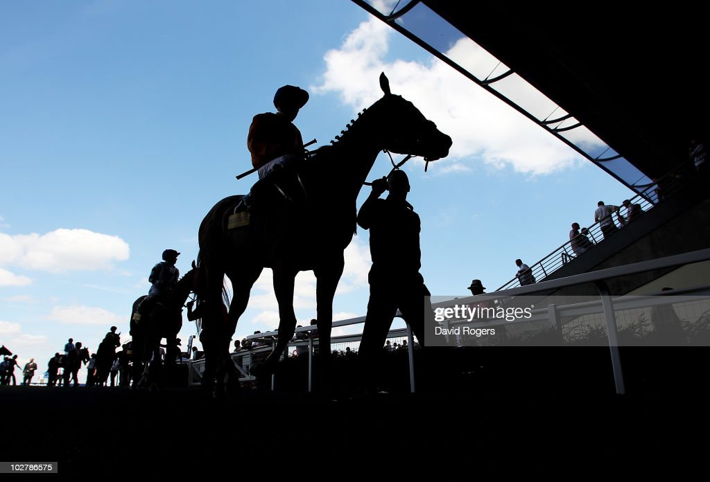 The horse and riders are led back to the unsaddling enclosure after the Totescoop6 handicap stakes at Ascot Racecourse on July 10, 2010 in Ascot, England.