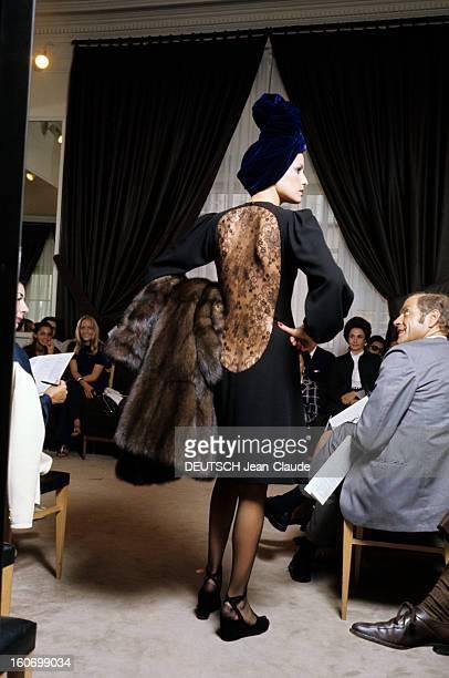 The House Of Couture Yvessaintlaurent In Paris Un mannequin portant une robe noire unie dont le dos est réalisé en dentelle noire dessinant une forme...