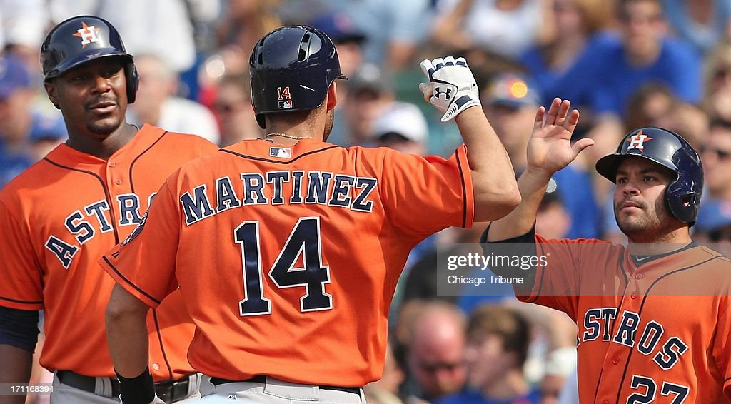 The Houston Astros' J.D. Martinez (14) gets high-fivea at home from teammates Chris Carter, left, and Jose Altuve after his three-run home run against the Chicago Cubs in the sixth inning at Wrigley Field in Chicago, Illinois, on Saturday, June 22, 2013. Houston won, 4-3.