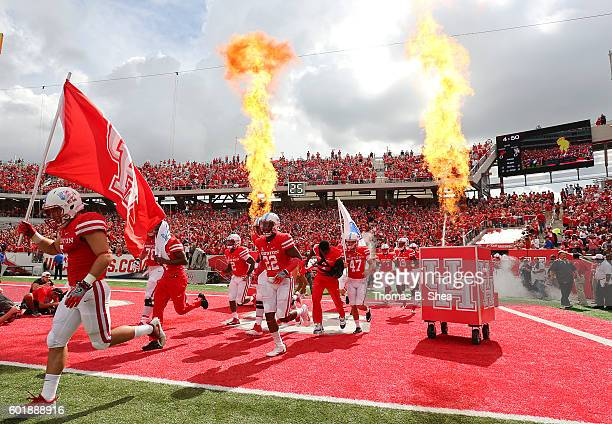 The Houston Cougars run onto the field before playing against the Lamar Cardinals at TDECU Stadium on September 10 2016 in Houston Texas