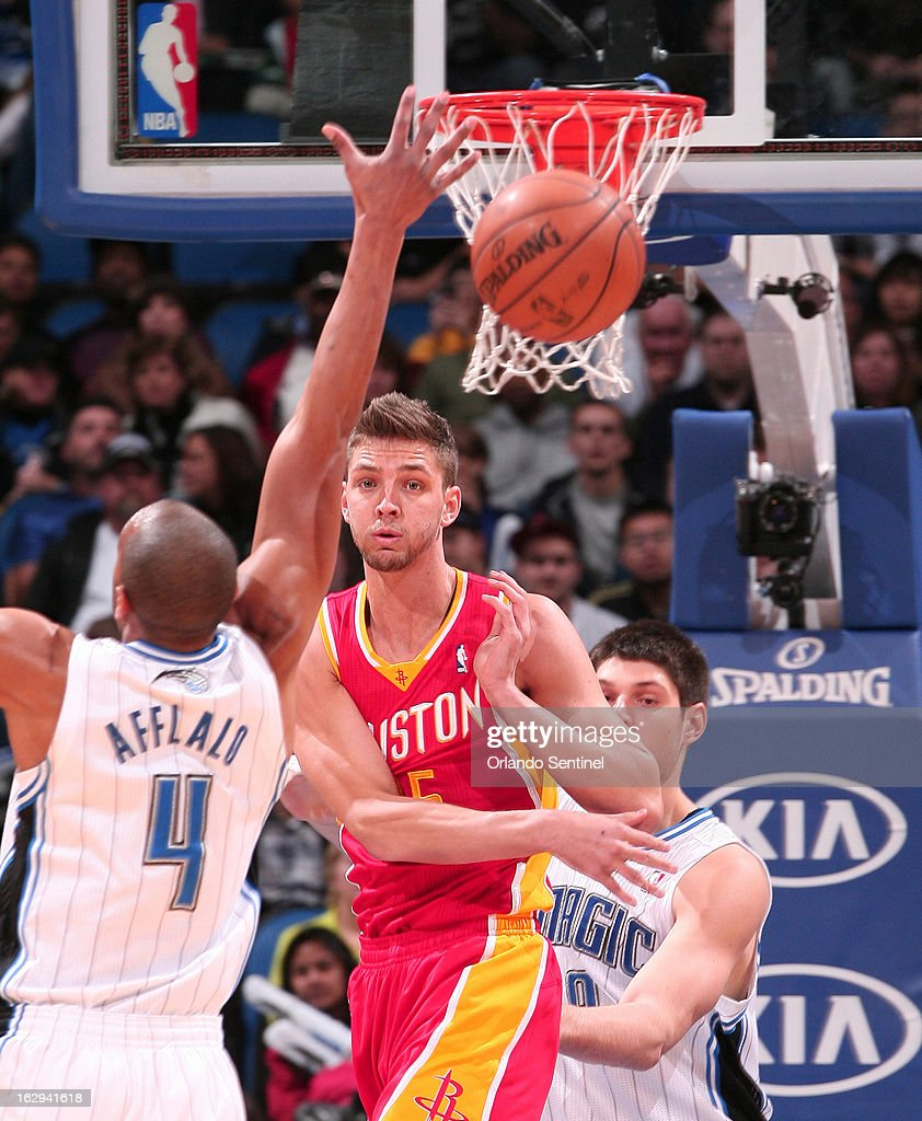 The Houston Rockets' Chandler Parsons (25) passes around the Orlando Magic's Arron Afflalo (4) during the first half at the Amway Center in Orlando, Florida, on Friday, March 1, 2013. Houston defeated Orlando, 118-110.