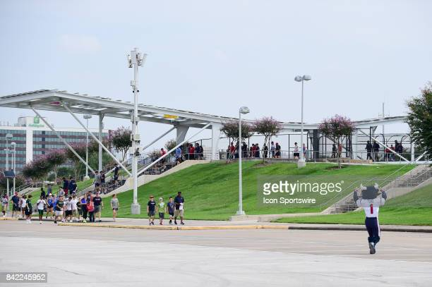 The Houston Texans and their families make their way over the bridge toward the press conference and busses as the Houston Texans mascot Toro cheers...