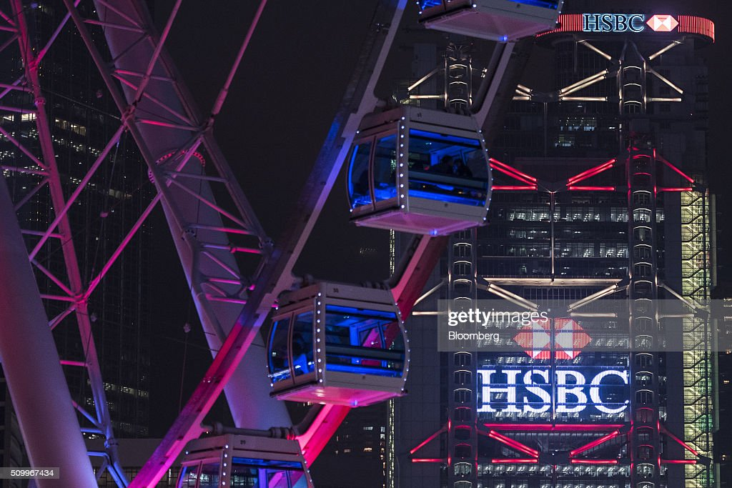 The HSBC Holdings Plc headquarters building stands behind the Hong Kong Observation Wheel at night in Hong Kong, China, on Saturday, February 13, 2016. HSBC's board will meet on Sunday to decide whether to shift its headquarters from London, according to two people with knowledge of the decision. Photographer: Xaume Olleros/Bloomberg via Getty Images
