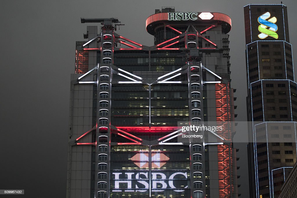 The HSBC Holdings Plc headquarters, center, and Standard Chartered Bank building, right, stand at night in Hong Kong, China, on Saturday, Feb. 13, 2016. HSBC's board will meet on Sunday to decide whether to shift its headquarters from London, according to two people with knowledge of the decision. Photographer: Xaume Olleros/Bloomberg via Getty Images