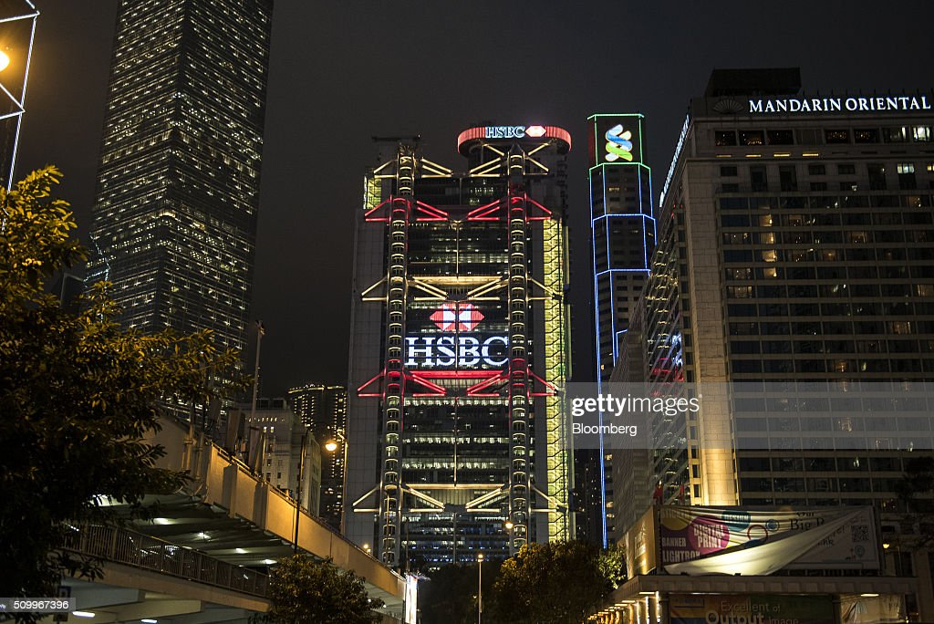 The HSBC Holdings Plc headquarters, center, stands next to the Standard Chartered Bank building and Mandarin Oriental Hotel, right, at night in Hong Kong, China, on Saturday, Feb. 13, 2016. HSBC's board will meet on Sunday to decide whether to shift its headquarters from London, according to two people with knowledge of the decision. Photographer: Xaume Olleros/Bloomberg via Getty Images