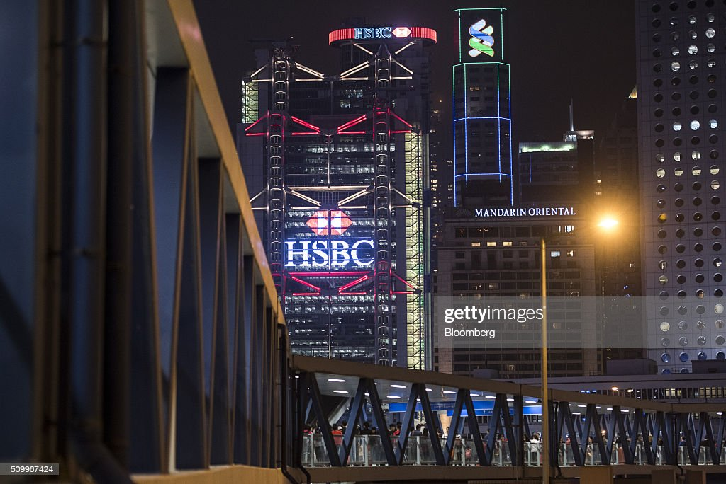 The HSBC Holdings Plc headquarters, left, stands next to the Standard Chartered Bank building and Mandarin Oriental Hotel, right, at night in Hong Kong, China, on Saturday, Feb. 13, 2016. HSBC's board will meet on Sunday to decide whether to shift its headquarters from London, according to two people with knowledge of the decision. Photographer: Xaume Olleros/Bloomberg via Getty Images