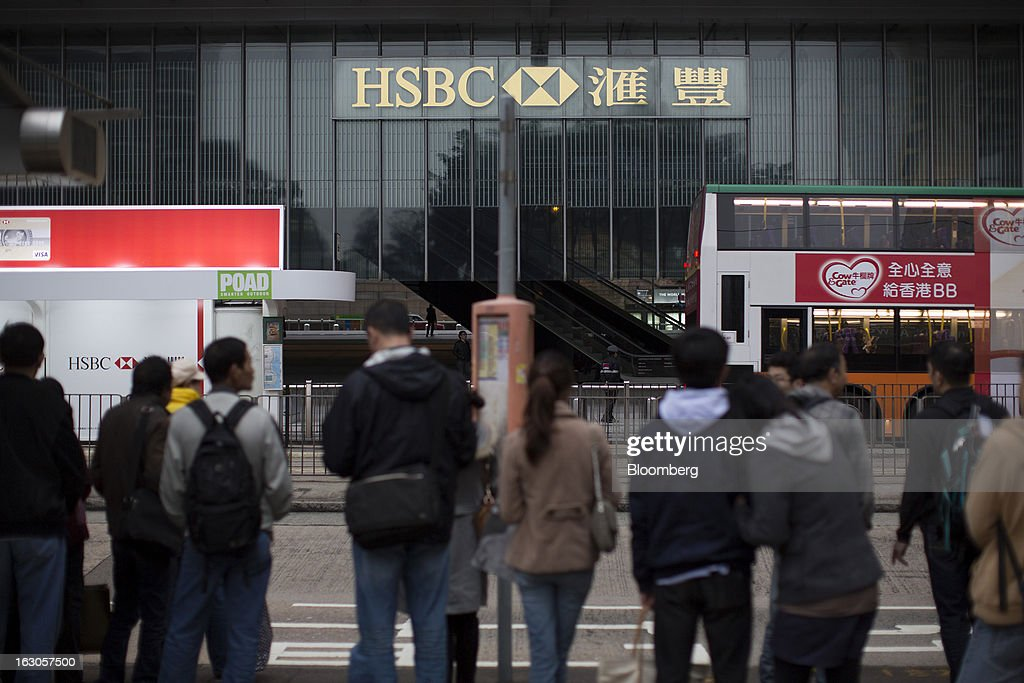 The HSBC Holdings Plc logo is displayed at the HSBC Main Building as commuters wait in line for buses in Hong Kong, China, on Saturday, March 2, 2013. HSBC is scheduled to release annual results on March 4. Photographer: Jerome Favre/Bloomberg via Getty Images
