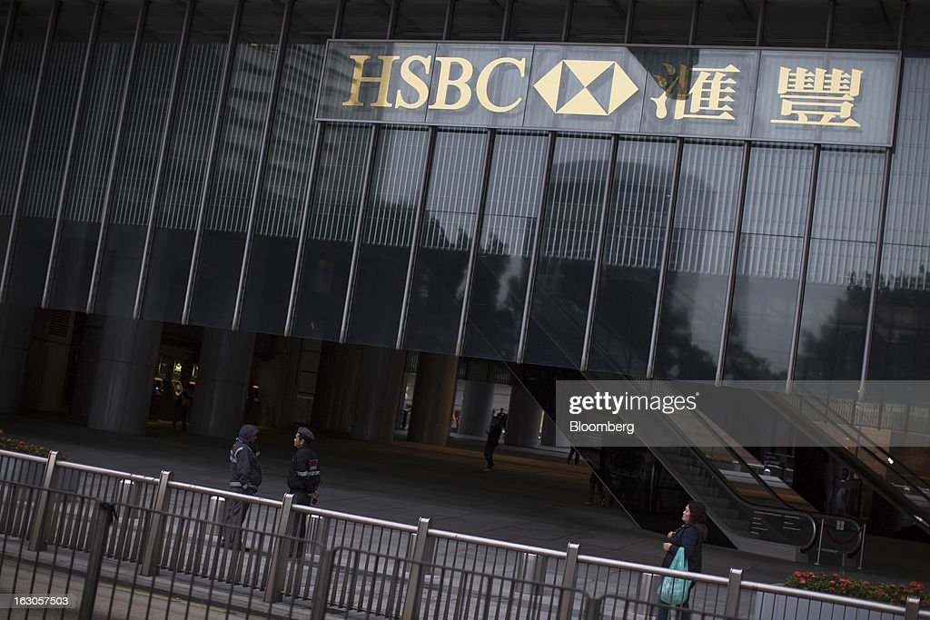 The HSBC Holdings Plc logo is displayed at the HSBC Main Building as security guards stand beneath in Hong Kong, China, on Saturday, March 2, 2013. HSBC is scheduled to release annual results on March 4. Photographer: Jerome Favre/Bloomberg via Getty Images