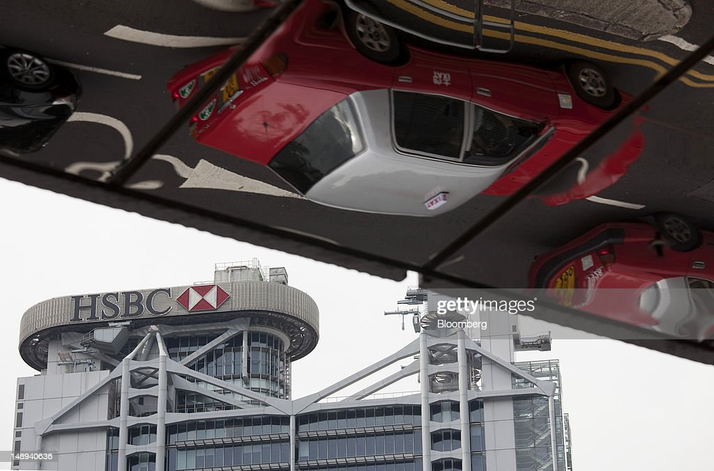 The HSBC Holdings Plc logo is displayed on top of the company's headquarters, left, as taxis are reflected on a buidling in Hong Kong, China, on Friday, July 20, 2012. Traders at Deutsche Bank AG, HSBC Holdings Plc, Societe Generale SA and Credit Agricole SA are under investigation for interest-rate manipulation in a global probe that led to a record fine for Barclays Plc last month, a person with knowledge of the matter said. Photographer: Jerome Favre/Bloomberg via Getty Images