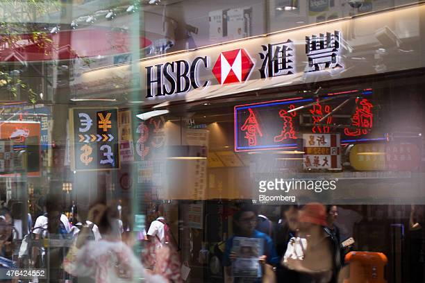 The HSBC Holdings Plc logo is seen through reflections on a glass window at a bank branch in Hong Kong China on Tuesday June 9 2015 HSBC will...
