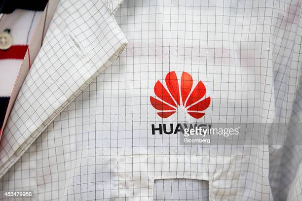 The Huawei Technologies Co logo is displayed on an engineer's lab coat inside the global compliance and testing center at the company's campus in the...
