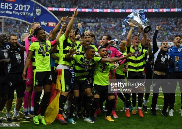 The Huddersield Town team celebrate with The Championship play off trophy after the Sky Bet Championship play off final between Huddersfield and...
