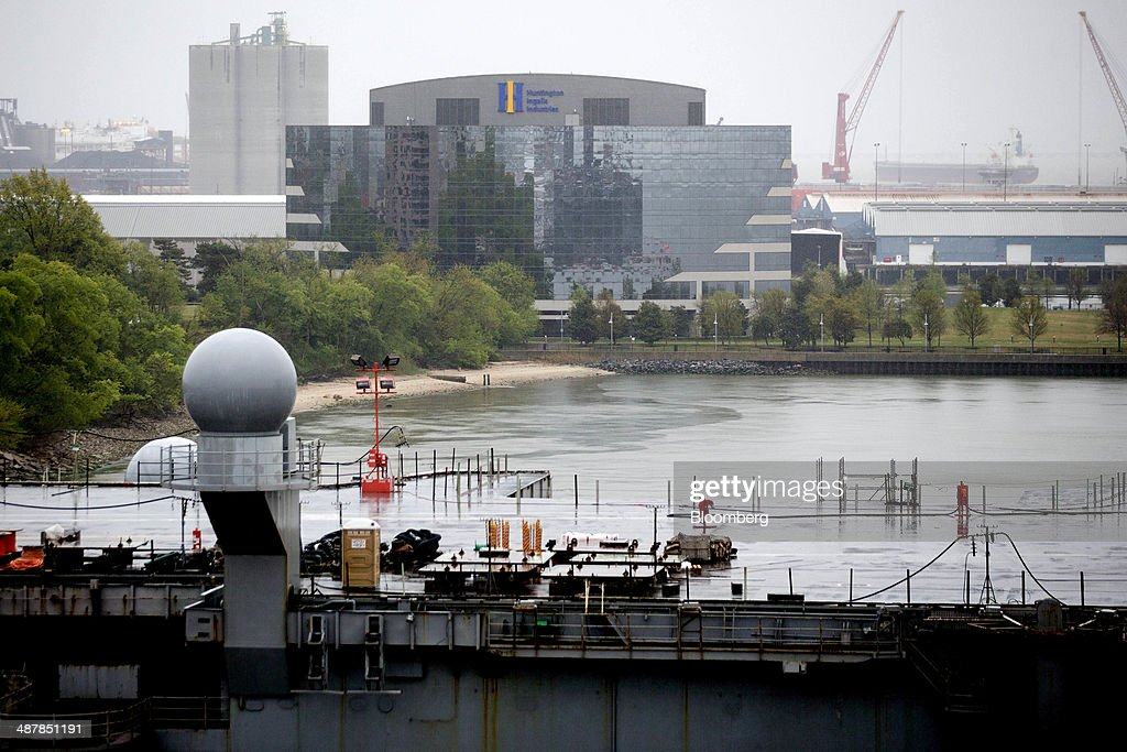 The Huntington Ingalls Industries Inc headquarters stands past the USS Enterprise aircraft carrier during inactivation at Huntington Ingalls...