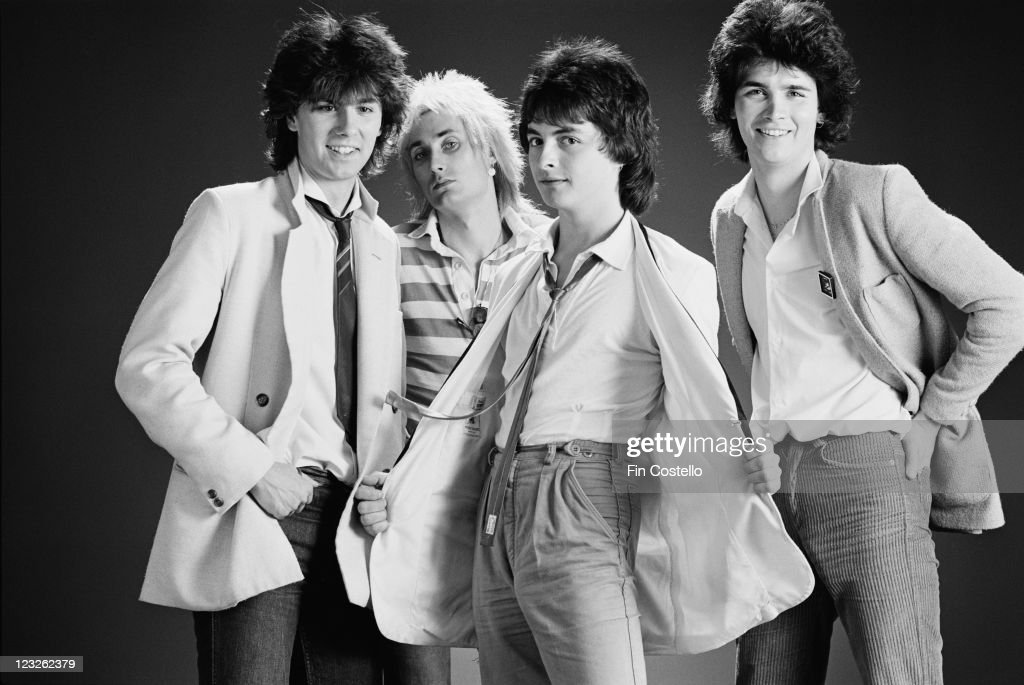 The Ian Mitchell Band (singer Ian Mitchell, bassist John Jay, guitarist Paul Jackson, drummer Lindsay Simon James Honey), British pop group, pose for a group studio portrait, against a black background, United Kingdom, in May 1979.