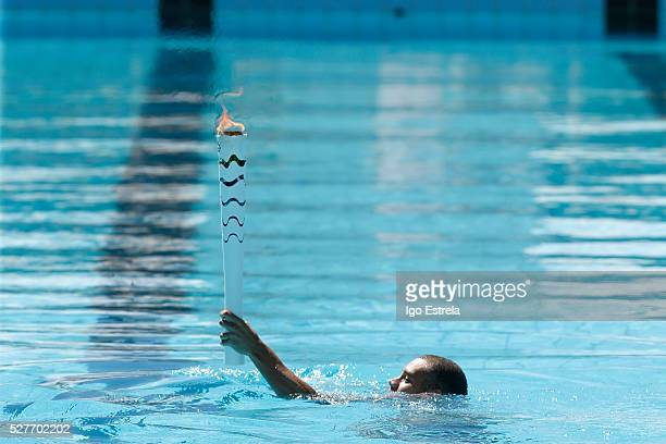 The Icarus Pereira swimmer takes the Olympic torch swimming in the pool water complex Claudio Coutinho on May 3 2016 in Brasilia Brazil The Olympic...