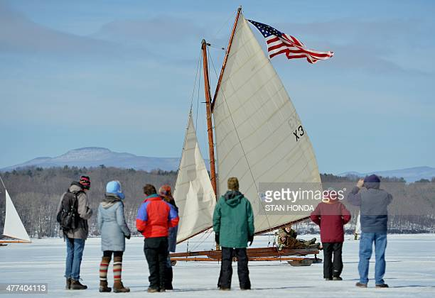 The ice boat Aurora sails past onlookers on a frozen Hudson River March 7 2014 in Barrytown New York These historic 'ice yachts' some dating to the...