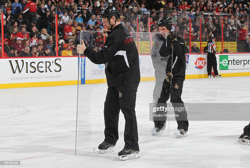 The ice crew changes a pane of broken glass during an NHL game between the Ottawa Senators and the Buffalo Sabres on February 5, 2013 at Scotiabank Place in Ottawa, Ontario, Canada.