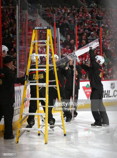 The ice crew replace a broken pane of glass during an NHL game between the Ottawa Senators and the Edmonton Oilers at Canadian Tire Centre on October...
