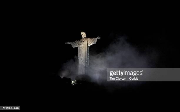 The iconic Cristo Redentor Christ the Redeemer statue appears out of the clouds while lit up at night time atop the mountain Corcovado The Christ...