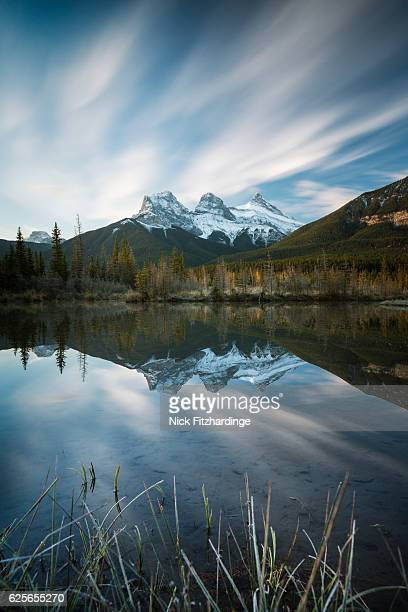 The iconic three sisters mountains reflected in a still pool, Canmore, Alberta, Canada