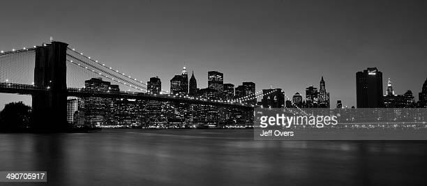The iconic view of Manhattan New York City seen from Brooklyn at night The Brooklyn Bridge runs across the East River in the foreground with the...