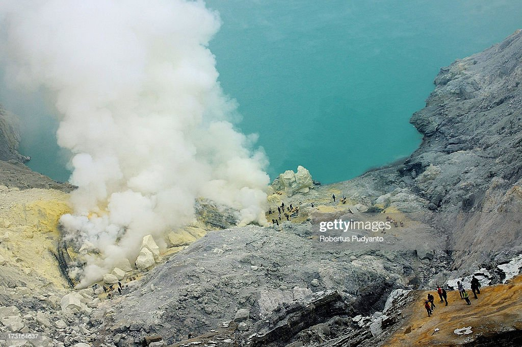 The Ijen Lake, which is about 20 kilometers wide and 200 meters deep is seen on July 9, 2013 in Arjuna, Java, Indonesia. Ijen Crater, which is known as Kawah Ijen, is located in the Ijen Volcano region, bordered by Banyuwangi and Bondowoso in East Java Province, Indonesia. Ijen Volcano is 2,600 meters tall (8,660 ft), topped with a large caldera and a 200 meter deep lake of sulfuric acid. The quietly active volcano emits gases through fumaroles inside the crater, and local miners have tapped those gases to earn a living. Stone and ceramic pipes cap the fumaroles, and inside the sulfur condenses into a molten red liquid, dripping back down and solidifying into pure sulfur. Miners hack chunks off with steel bars, braving extremely dangerous gases and liquids with minimal protection, then load up as much as they can carry for the more than 3 kilometers to the weighing station. Loads can weigh from 50 to 90 kg (100 - 200 lbs), and a single miner might make as many as two or three trips return in a day. At the end of a long day, miners take home approximately Rp. 50,000. The sulfur is then used for vulcanizing rubber, bleaching sugar and other industrial processes nearby. Sulfur widely used in fertilizer industry, cosmetics, skin disease drug, insecticides, paper, paints, plastics, petroleum processing, rubber and tire industry, sugar industry, batteries, chemicals industrial, explosives, weaving, film and photography, and also in metal or steel industry.