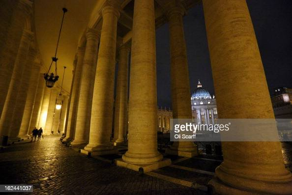 The illuminated Basilica is seen through the colonnade in Saint Peter's Square is on February 23 2013 in Vatican City Vatican Pope Benedict XVI is...