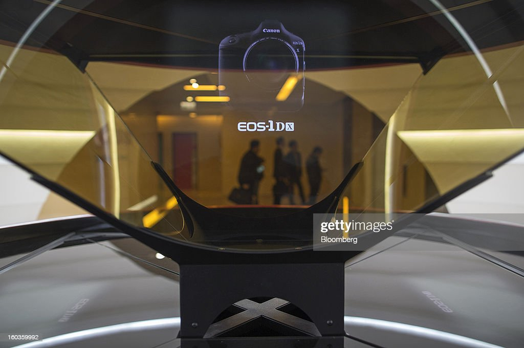 The image of a Canon Inc. EOS-1D X digital single lens reflex (SLR) camera is projected inside a holographic display case at the company's showroom in Hong Kong, China, on Tuesday, Jan. 29, 2013. Canon, the world's largest camera maker, forecast profit will rise 14 percent this year amid a weaker yen and the withering of a boycott of Japanese goods in China. Photographer: Jerome Favre/Bloomberg via Getty Images