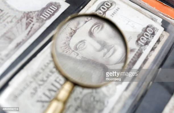 The image of the Greek god Apollo is seen through a magnifying glass on an old Greek one thousand drachma banknote as it sits on display at a street...