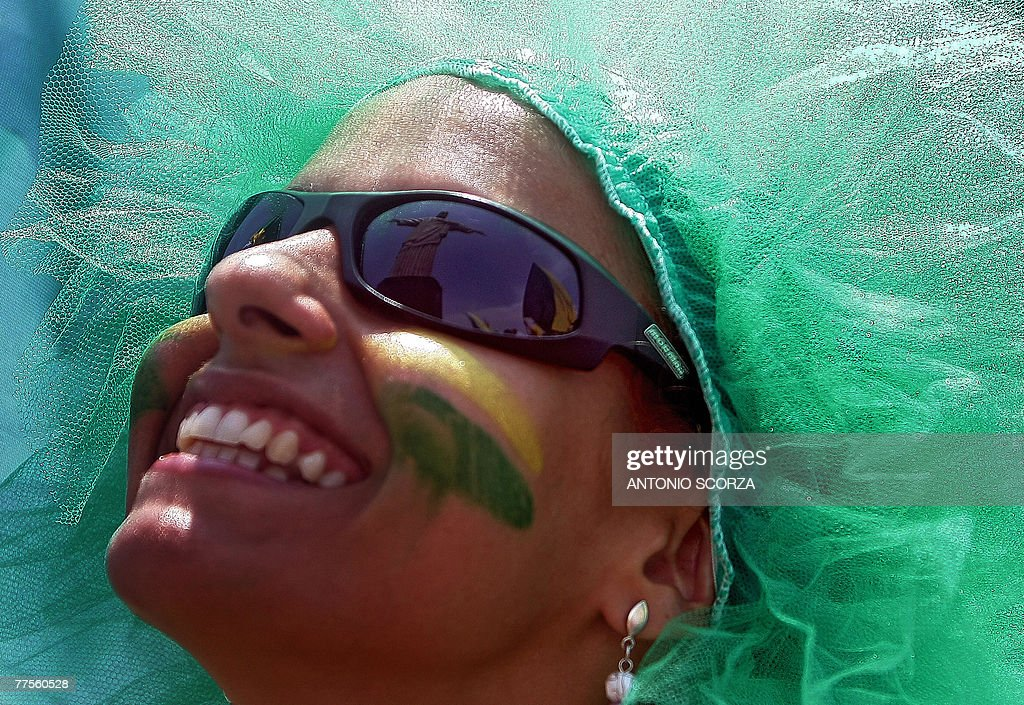The image of the statue to Christ the Redeemer reflects on the sunglasses of a football fan 30 October, 2007 in Rio de Janeiro, Brazil. Brazil, the only runner in the race, was officially unveiled as the 2014 World Cup host by FIFA president Sepp Blatter in Zurich Tuesday. The five-time world champions have staged the World Cup once before, in 1950, when they lost the final 2-1 to Uruguay in front of a near 200,000 crowd at the Maracana stadium in Rio de Janeiro. AFP PHOTO ANTONIO SCORZA