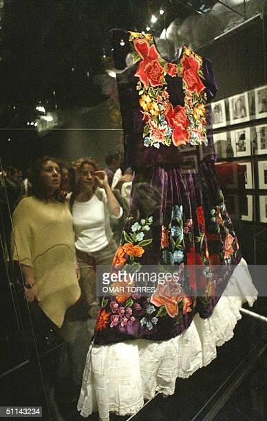 The image of two women reflects on the glass of a glass cabinet which holds a dress of Mexican painter Frida Kahlo on display during the opening of...