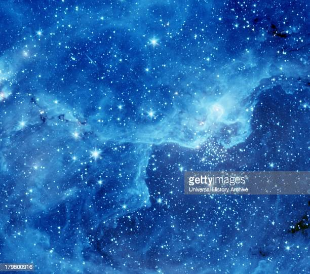 The image shows a cloud known as DR22 bursting with new stars in the Cygnus region of the sky Spitzer