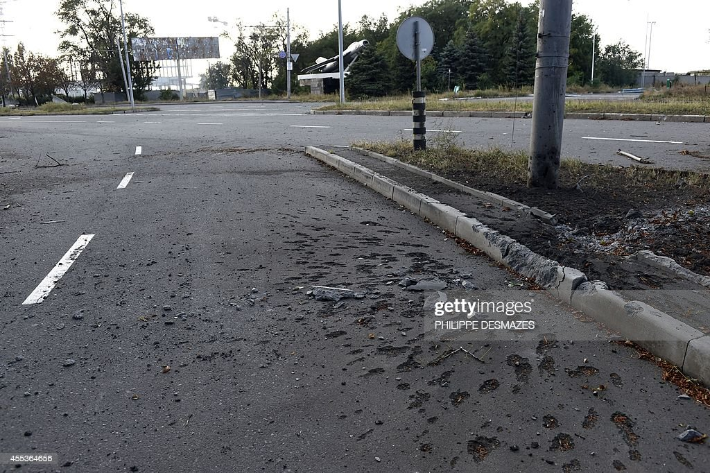 The impact of rocket scares the road leading to Donetsk International Airport on September 13 as shelling continues between proRussian forces and the...