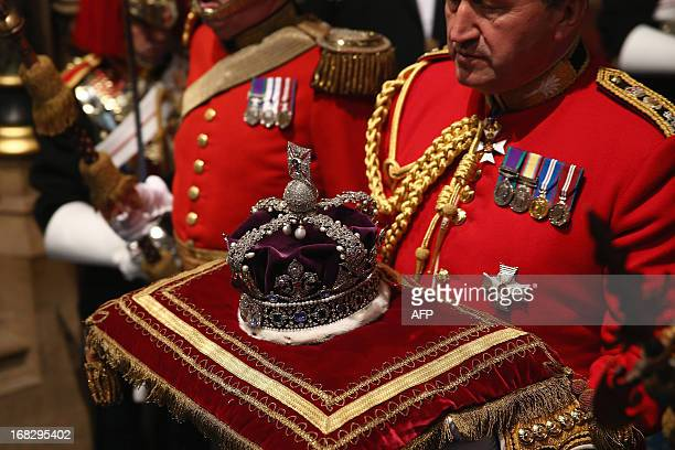 The Imperial State Crown is carried through the Norman Porch of the Palace of Westminster ahead of the State Opening of Parliament on May 8 2013 in...