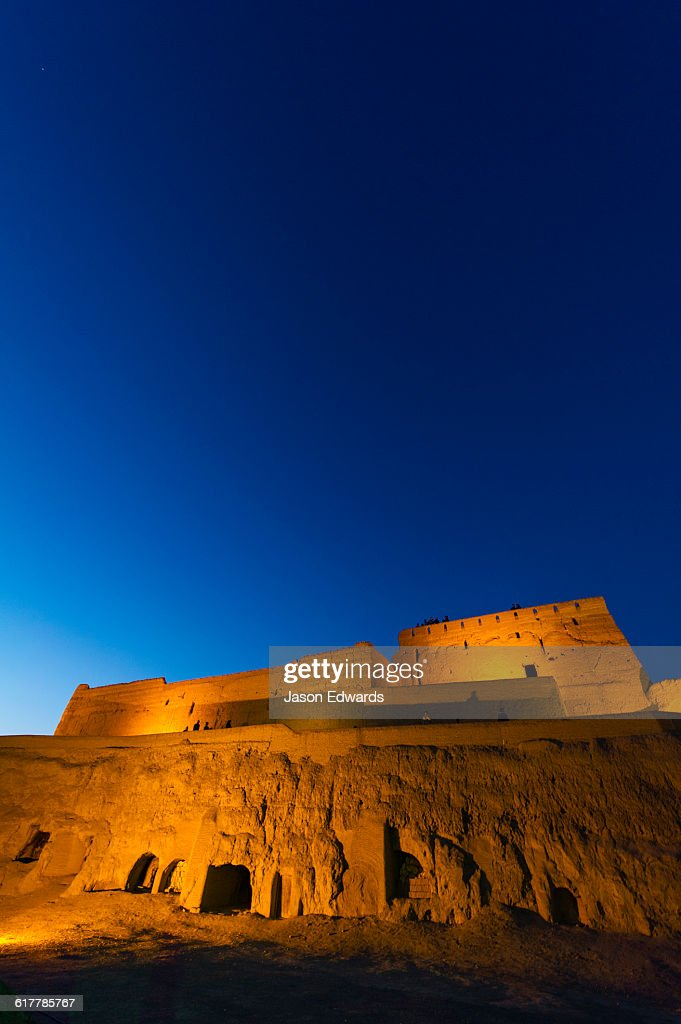 The imposing walls of an ancient mud brick fortress rising into the desert sky at night.
