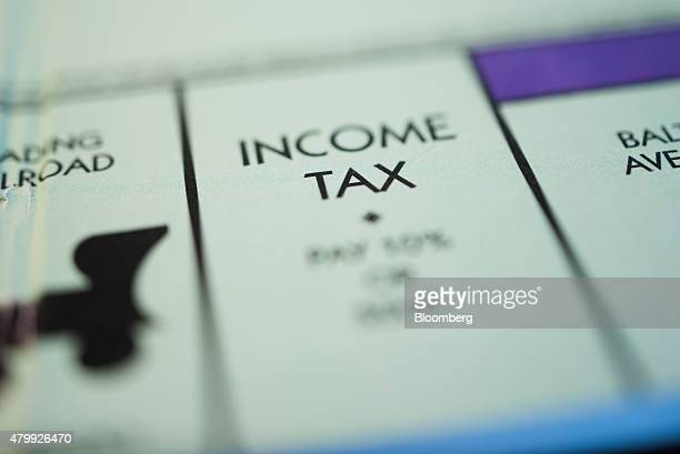 The 'Income Tax' square is seen on a Hasbro Inc Monopoly board game arranged for a photograph taken with a tiltshift lens in Oradell New Jersey US on...