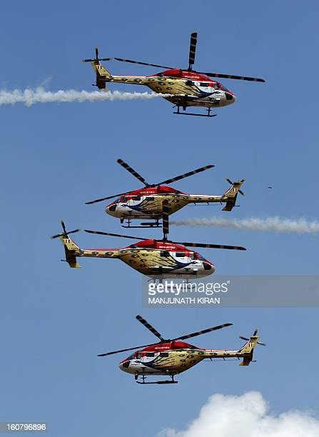 The Indian Air Force Sarang aerobatics team perform in their HAL Dhruv helicopters during Aero India 2013 at the Yelahanka Air Force station in...
