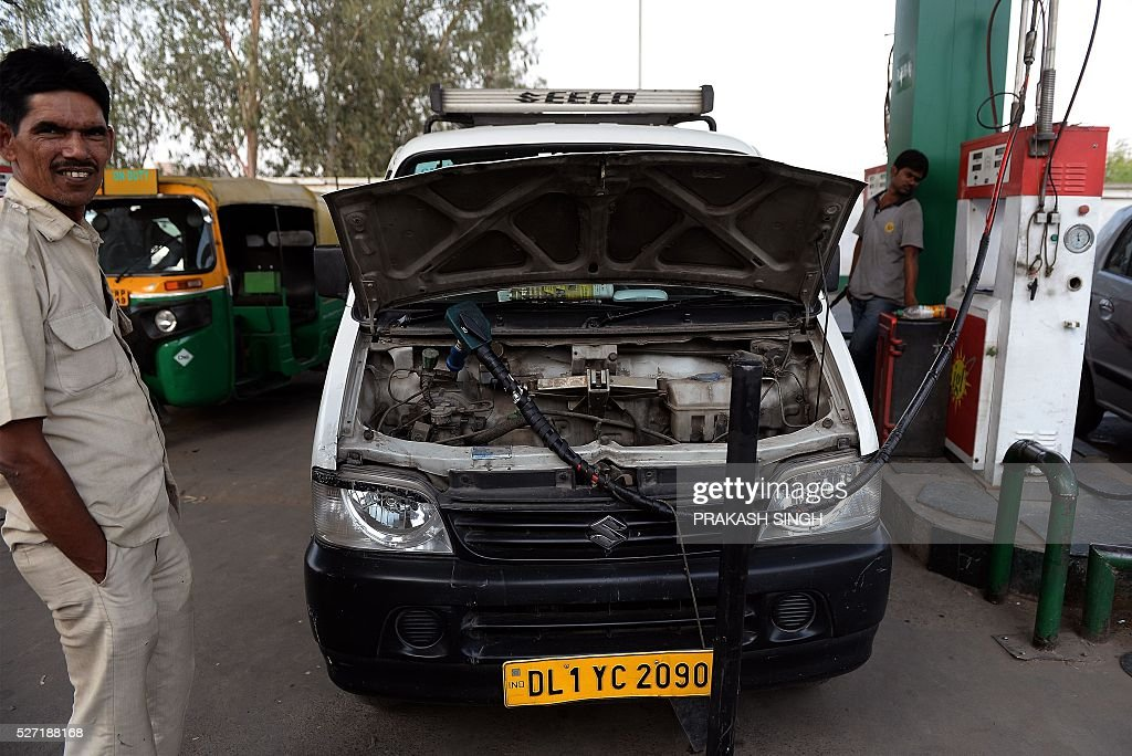 The Indian driver of a compressed natural gas (CNG)-run taxi car waits as his vehcile is filled with CNG in New Delhi on May 2, 2016. Hundreds of taxi drivers took to the streets of New Delhi to protest a court order banning diesel cabs from plying the roads of the world's most polluted capital. The ban would impact some 27,000 diesel taxis registered in Delhi, including app-based cab operators Ola and Uber. / AFP / PRAKASH