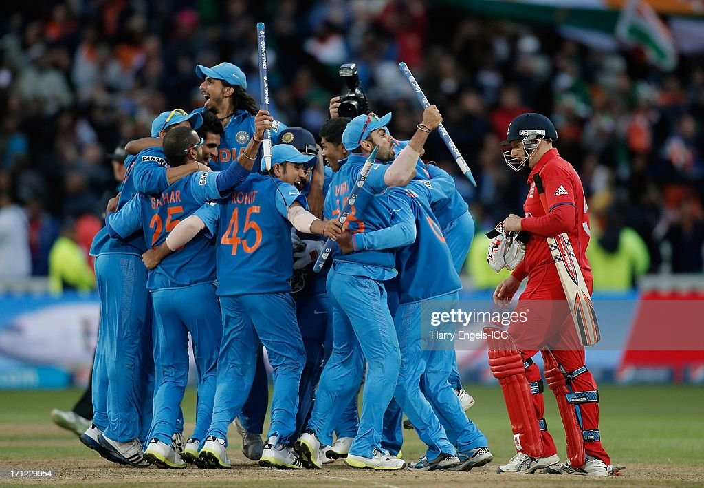 The Indian team celebrate as James Tredwell (R) of England looks dejected after the ICC Champions Trophy final between England and India at Edgbaston on June 23, 2013 in Birmingham, England.