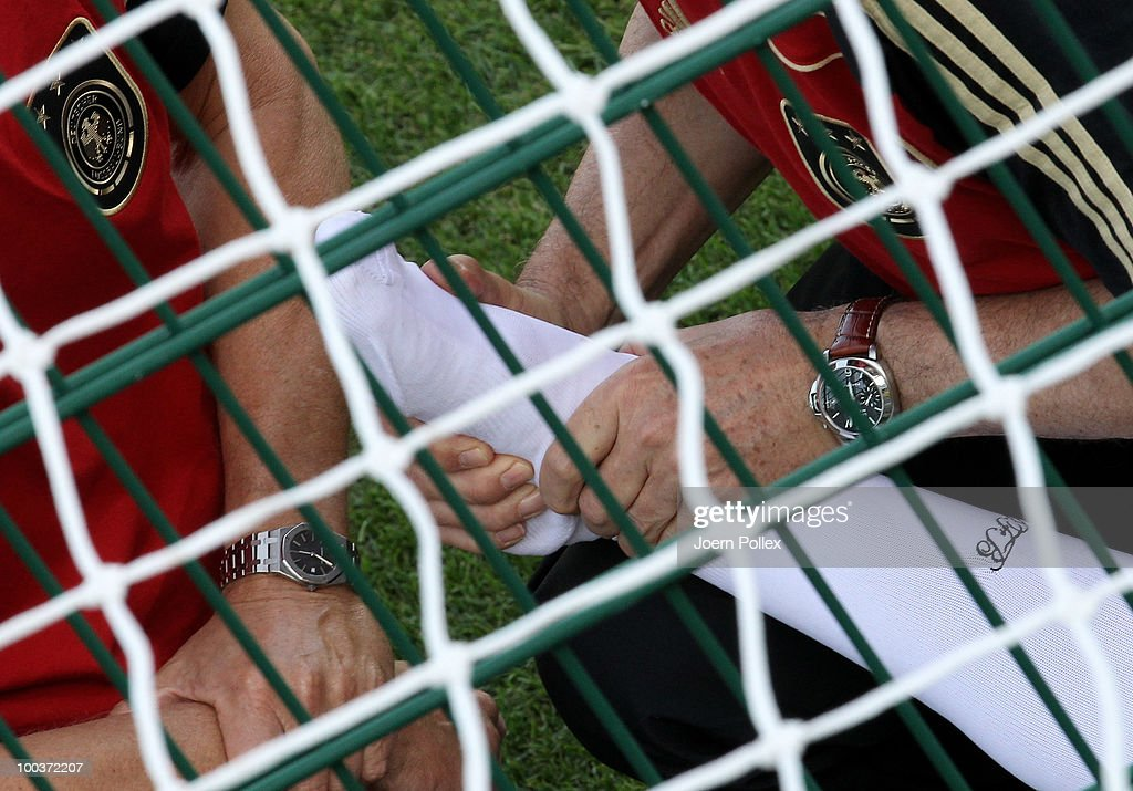 The injured ankle of Christian Traesch of Germany is seen held by Hans Wilhelm Mueller-Wohlfarth during the friendly match of FC South Tyrol and Germany at Sportzone Rungg on May 24, 2010 in Appiano sulla Strada del Vino, Italy.