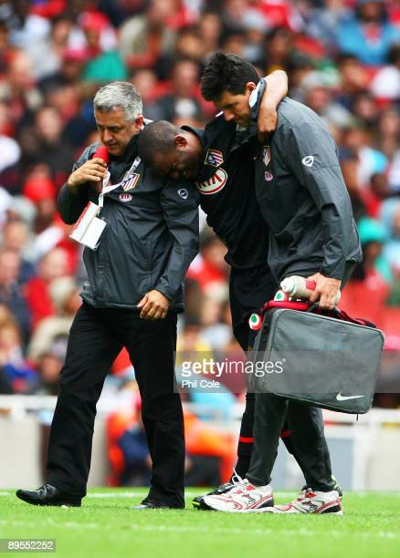 The injured Florent SinamaPongolle of Athletico is helped from the pitch during the Emirates Cup match between Arsenal and Athletico Madrid at the...