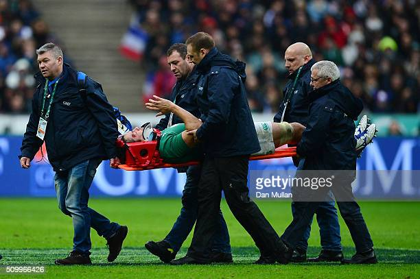 The injured Mike McCarthy of Ireland waves to the fans as he is stretchered off the pitch during the RBS Six Nations match between France and Ireland...
