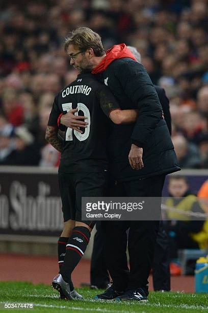 The injured Philippe Coutinho of Liverpool is hugged by Jurgen Klopp the Manager of Liverpool as leaves the pitch due to injury during the Capital...