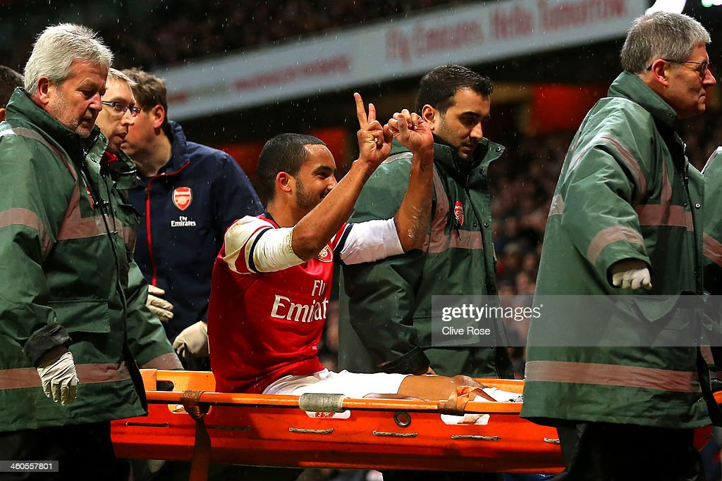 The injured <a gi-track='captionPersonalityLinkClicked' href=/galleries/search?phrase=Theo+Walcott&family=editorial&specificpeople=451535 ng-click='$event.stopPropagation()'>Theo Walcott</a> of Arsenal makes a 2-0 gesture to the Tottenham fans as he is stretchered off the pitch during the Budweiser FA Cup third round match between Arsenal and Tottenham Hotspur at Emirates Stadium on January 4, 2014 in London, England.