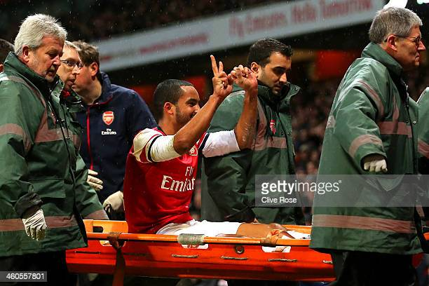 The injured Theo Walcott of Arsenal makes a 20 gesture to the Tottenham fans as he is stretchered off the pitch during the Budweiser FA Cup third...
